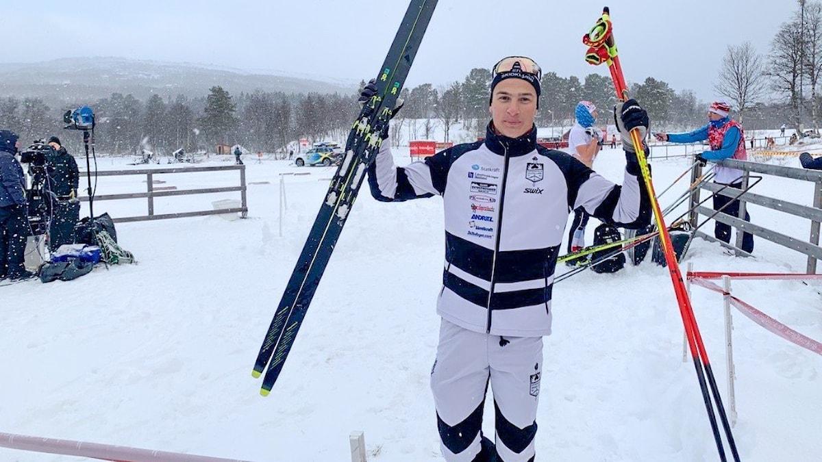 En man i skiddress håller upp stavar och skidor i luften.