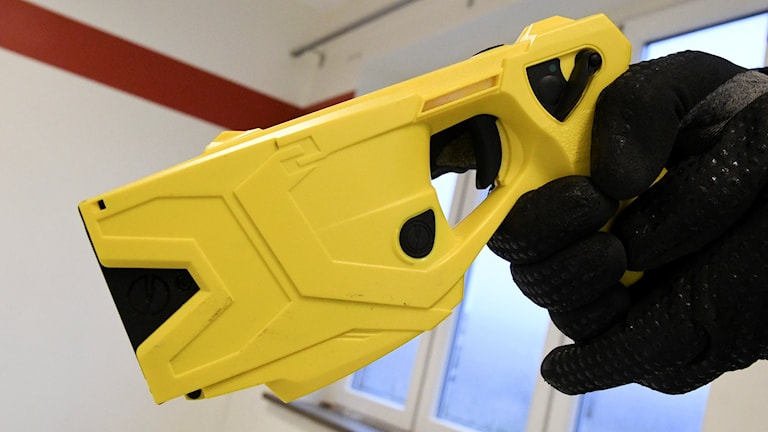 Hand som håller i ett elchocksvapen.