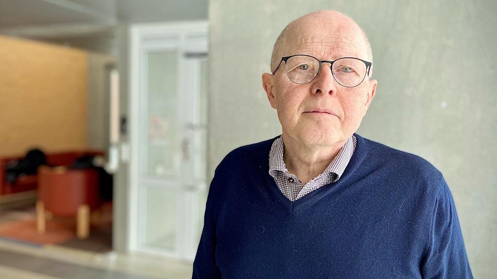 En äldre flintskallig man med glasögon i ett stort rum