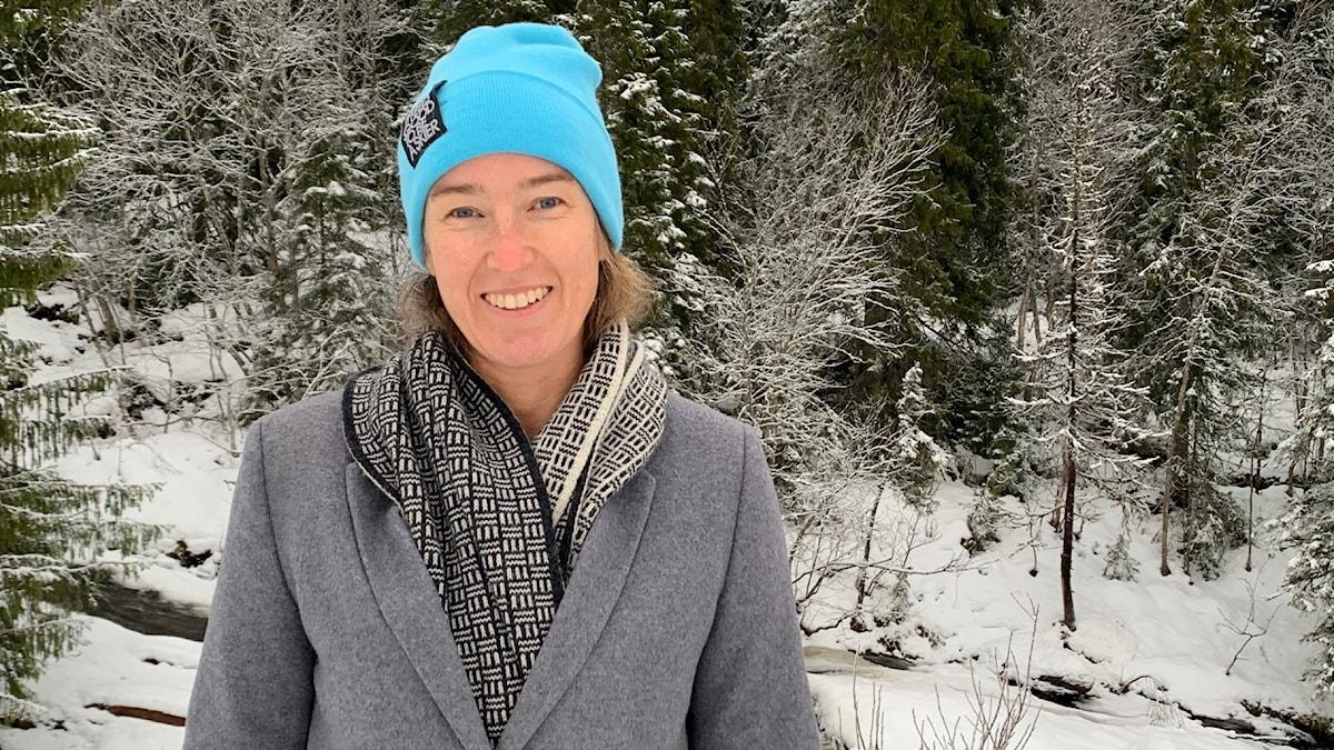 Leende kvinna i mössa och kappa i snöig skog