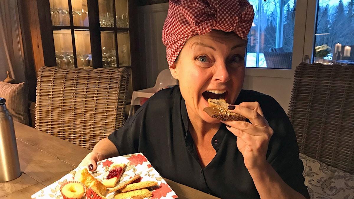 en kvinna med huckle som äter kakor