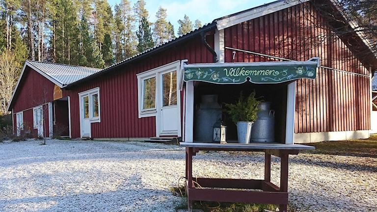 Exteriör enplanshus med rödmålad träfasad och mjölkbrygga med välkomstskylt