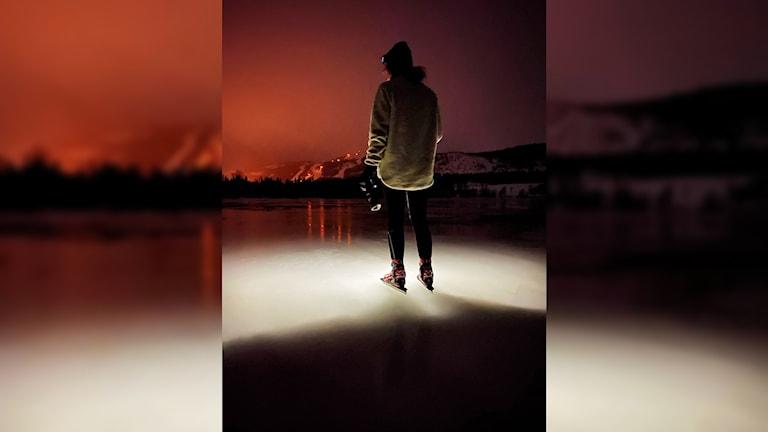 Skridskoåkare på sjöis i mörker med rött ljussken på himlen