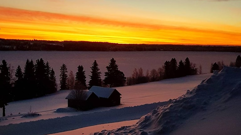 Solnedgång över sjö vintertid