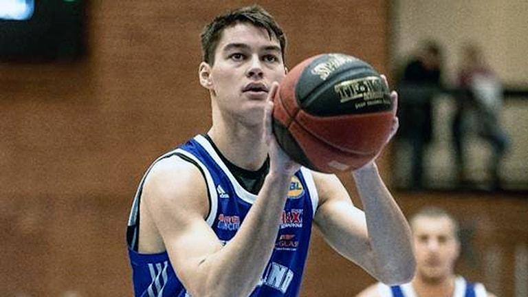 Basketspelare med boll i händerna