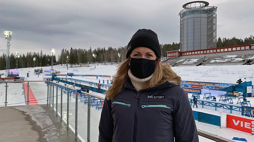 Kvinna iförd toppluva och munskydd, med vattentornet vid skidstadion i Östersund i bakgrunden.
