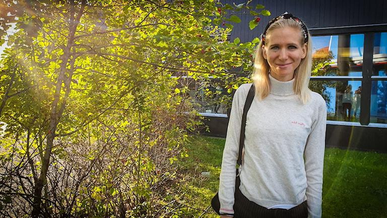 En blond kvinna står utomhus i solljuset.