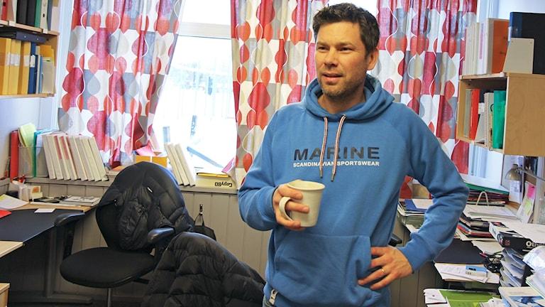 Man med kaffekopp i handen står i kontorsrum