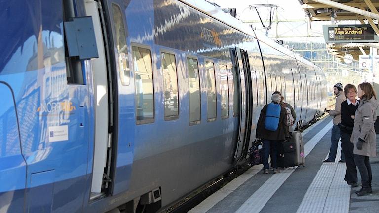 Blått tåg på järnvägsstation med resenärer på plattformen