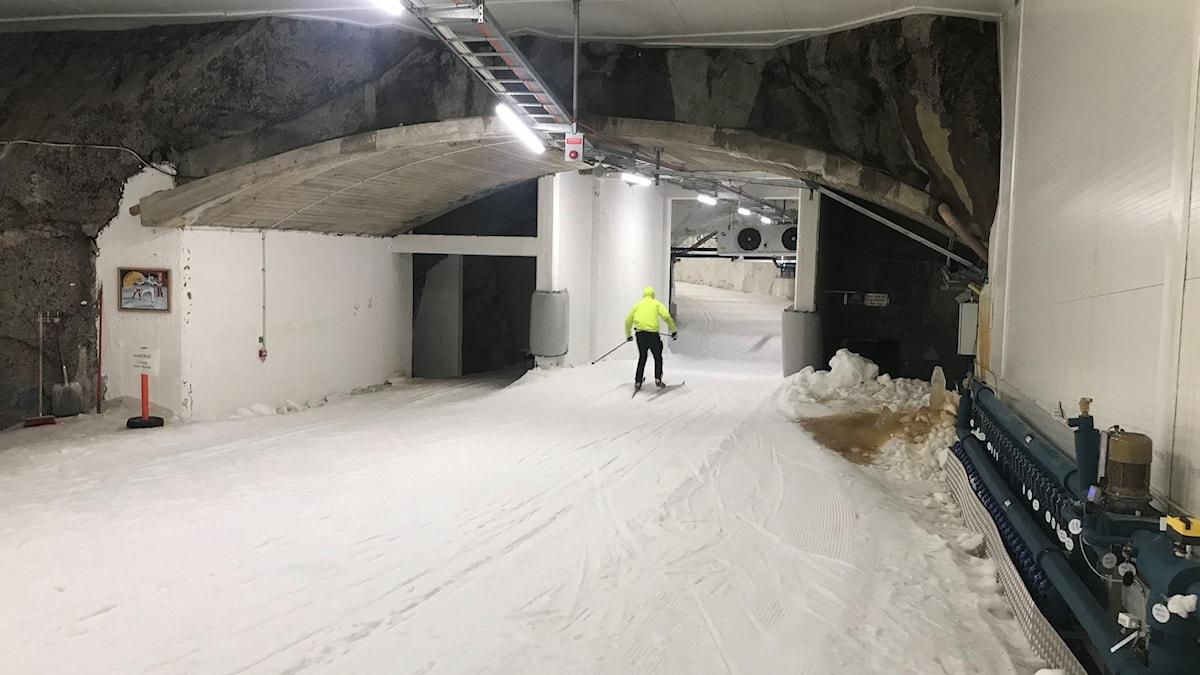 Skidåkare åker i tunnel med skidspår
