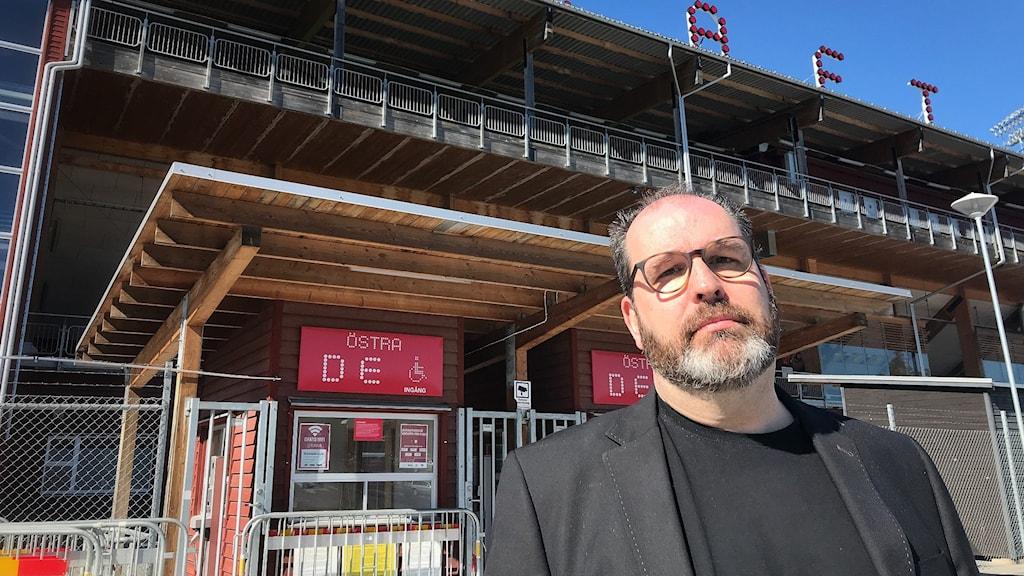 En man står framför Jämtkrafts fotbollsarena.