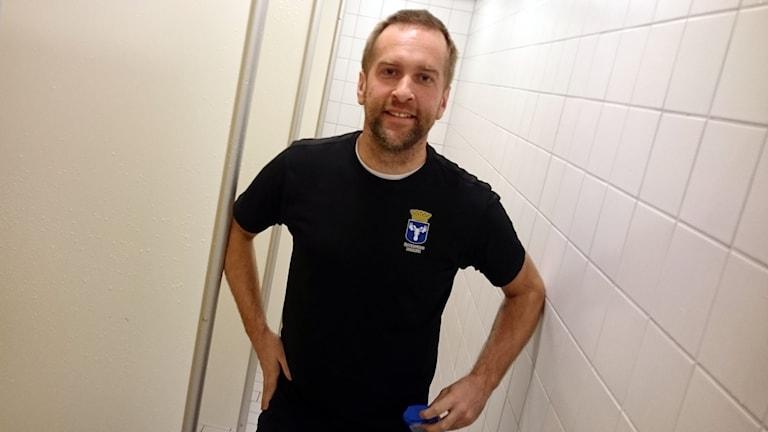 En påklädd man står i ett duschrum och visar upp lokalerna.