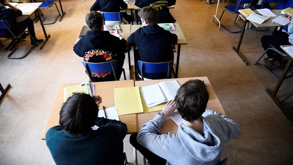 Elever sitter vid skolbänkar
