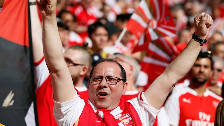 Arsenalsupporter med armarna i luften på läktaren