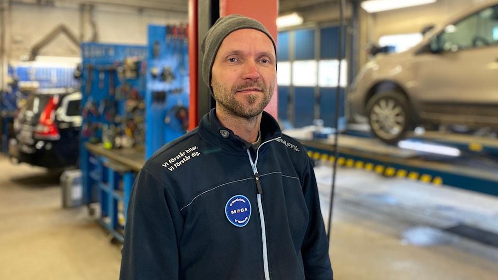 Man i marinblå jacka och mössa står inne i verkstadslokal med bilar och hyllor med verktyg