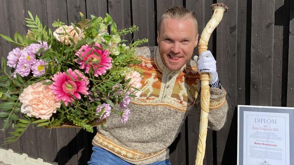 Man med en stor bukett blommor och en trästav i handen.