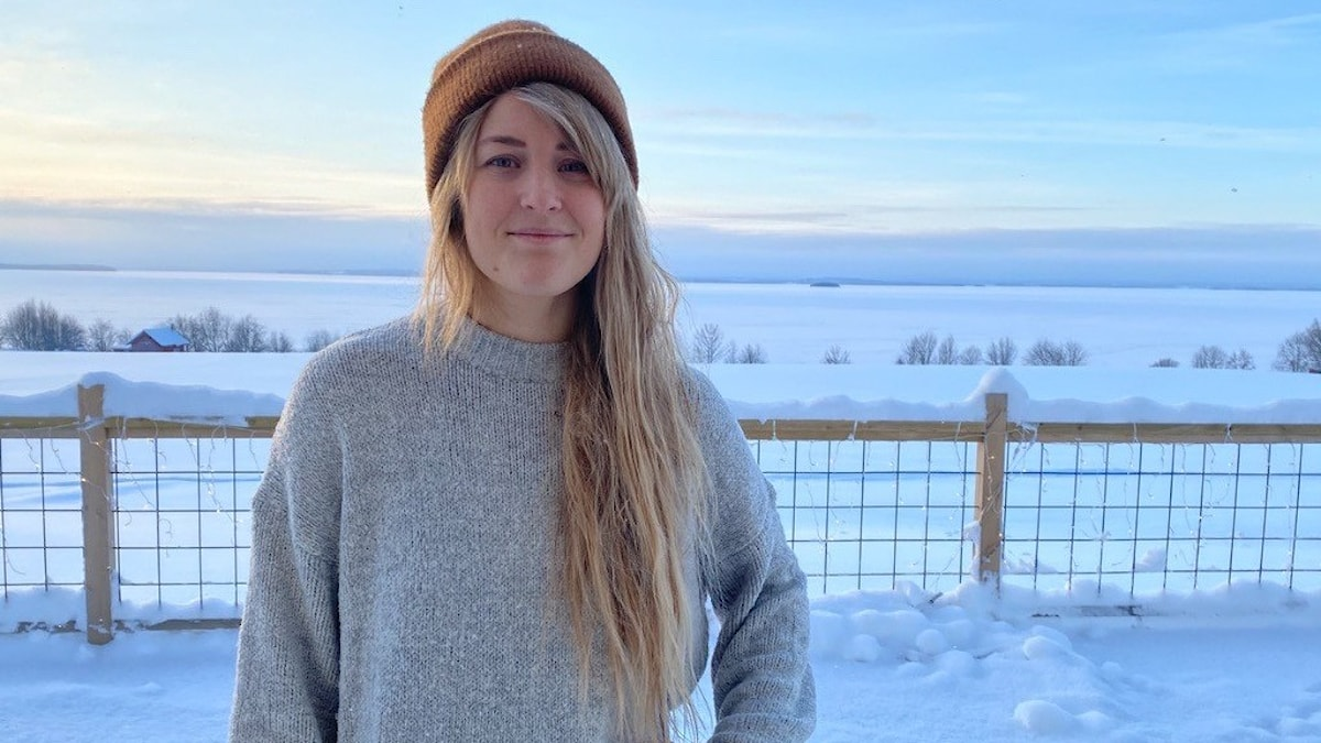 En kvinna med långt hår i stickad tröja och mössa med snötäckt landskap i bakgrunden