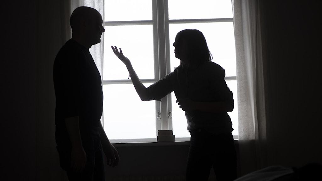 Mörk bild där en man och en kvinna pratar med varandra. Kan tolkas som ett bråk.