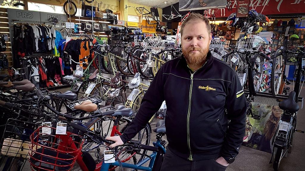 Man med skägg lutar sig mot en cykel, omgiven av många andra cyklar inne i en cykelaffär.