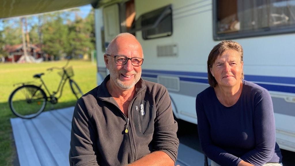 En man och en kvinna som sitter utanför en husvagn.