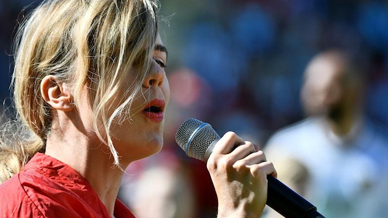 Kvinna med blont hår sjunger i mikrofon