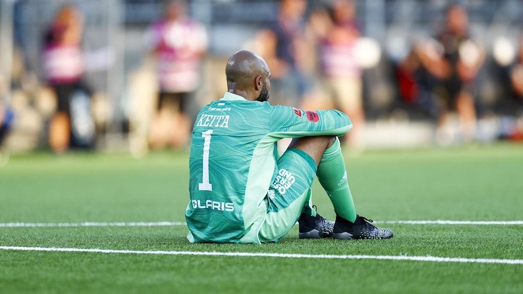 Fotbollsspelare i grön tröja sitter på gräset.