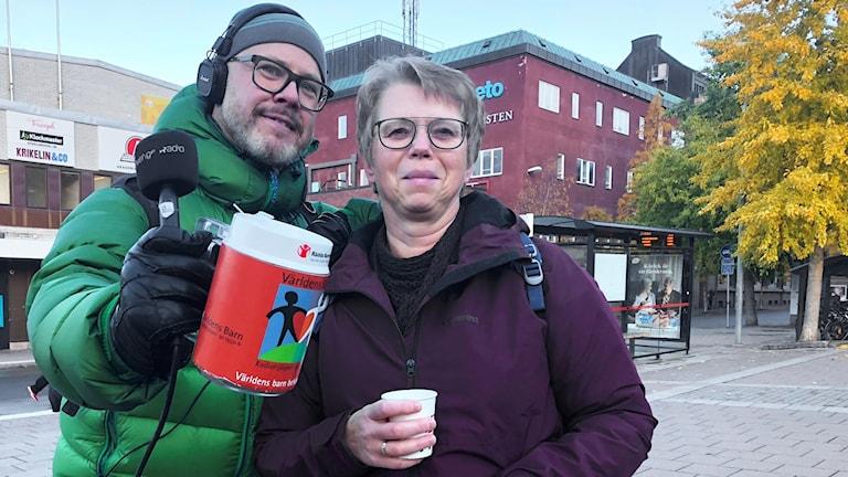 En man står med en insamlingsbössa och håller om en kvinna