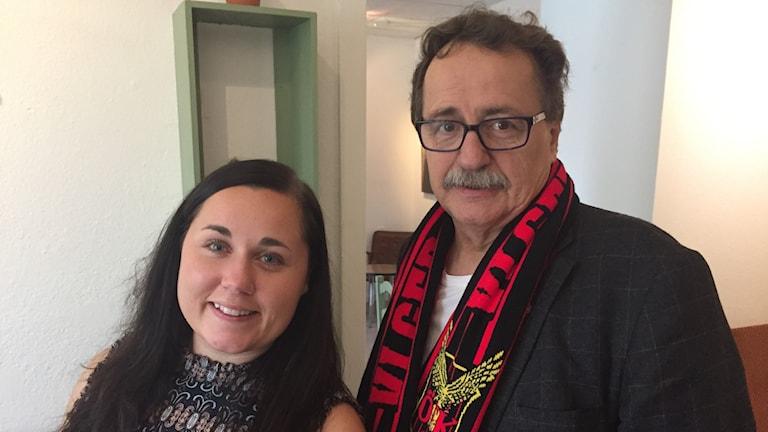 En kvinna och en man står bredvid varandra, mannen bär fotbollshalsduk.