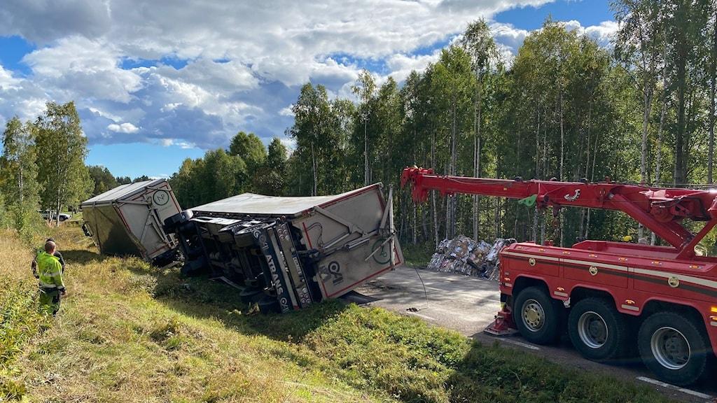 En bärgningsbil bärgar ett lastbilssläp längs en väg
