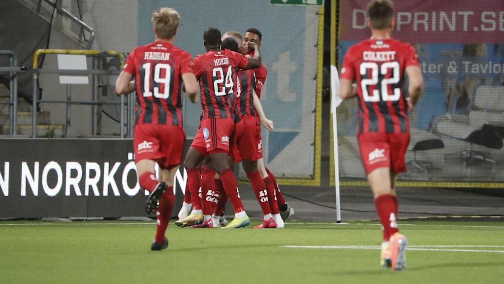 Fotbollsspelare i röd-svarta tröjor jublar.