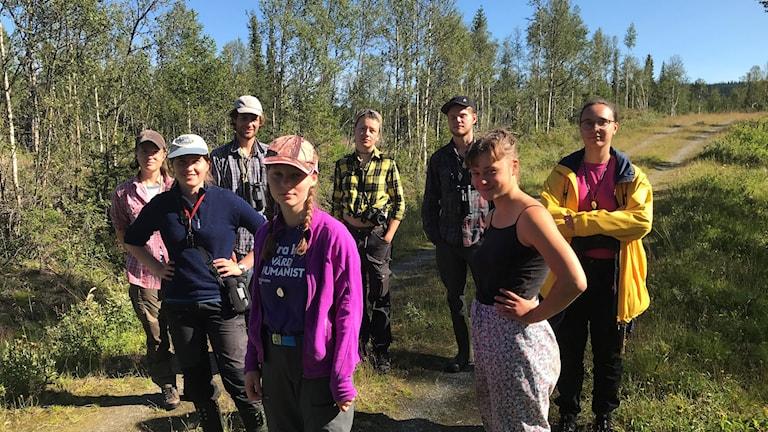 Ett gäng personer i 20-årsåldern står på en grusväg i skogen.