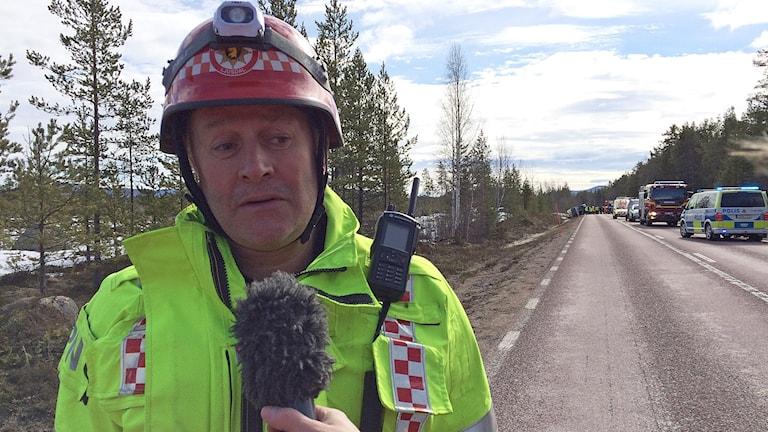Räddningstjänsteman står vid vägen vid trafikolycka