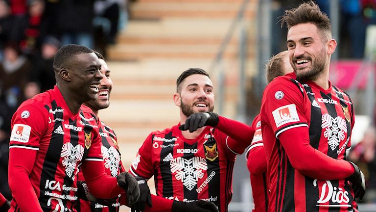 En grupp fotbollsspelare i rödsvartrandiga tröjor