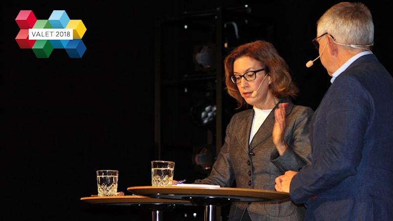 En kvinnlig programledare står på en scen och ställer en fråga.