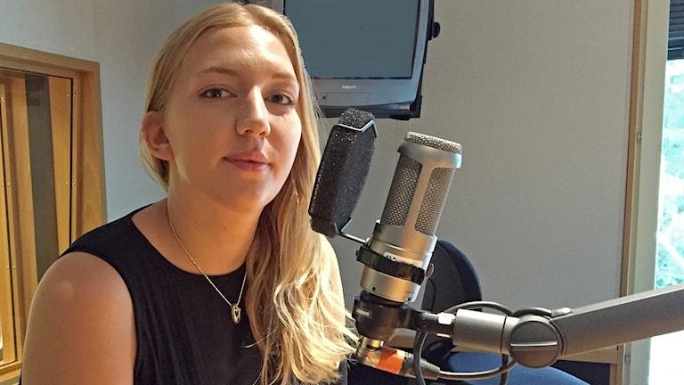 Ung blond kvinna sitter vid mikrofon i en radiostudio