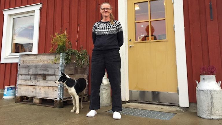 Kvinna med hund står framför ytterdörr på falurött hos med mjölkkruka bredvid