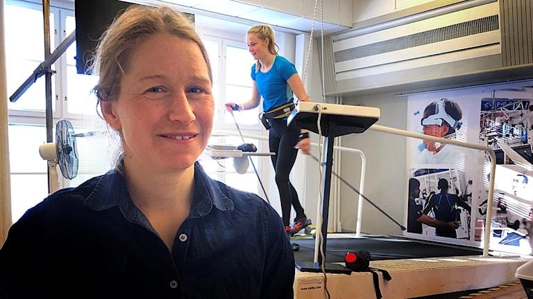 Martina Höök står framför ett löpband som en tjej åker rullskidor på.