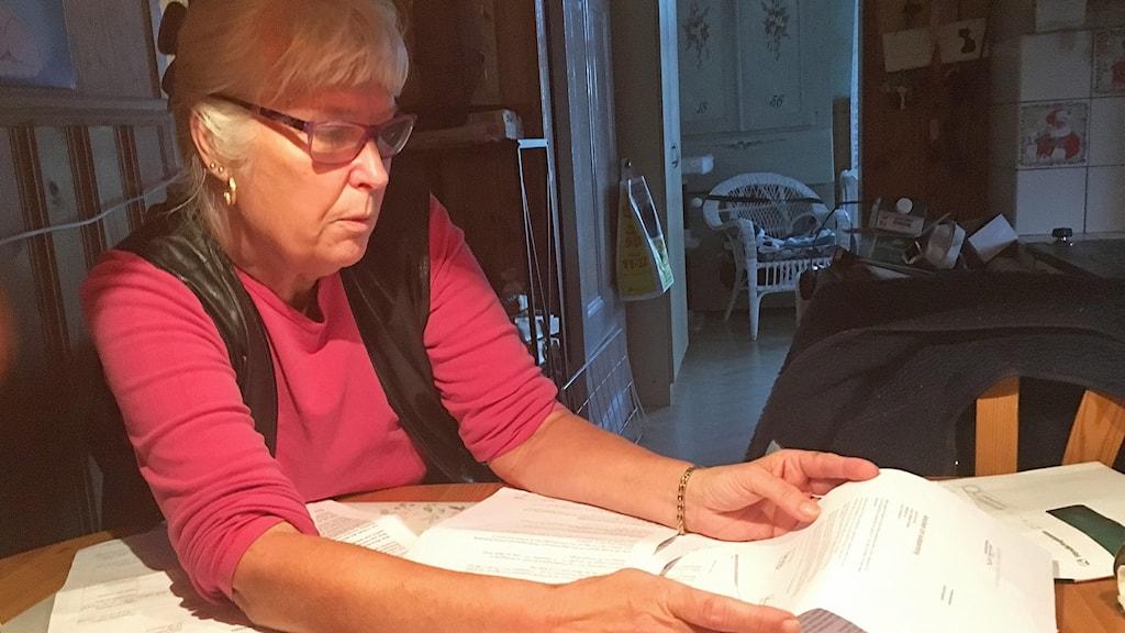 Äldre kvinna sitter med brev från Försäkringskassan framför sig på bordet