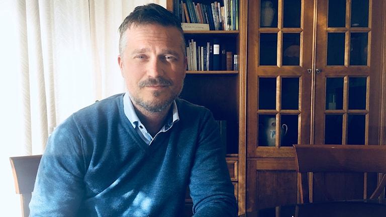 Man i tröja och skjorta sittande framför ett brunt vintrinskåp