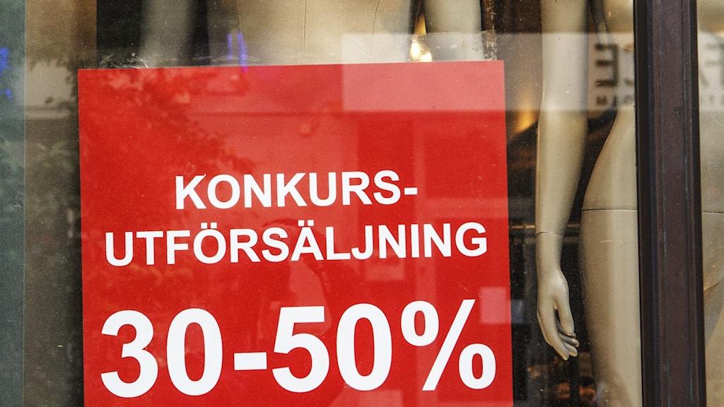 """Stor röd affisch """"Konkursutförsäljning"""" i skyltfönster med nakna skyltdockor"""