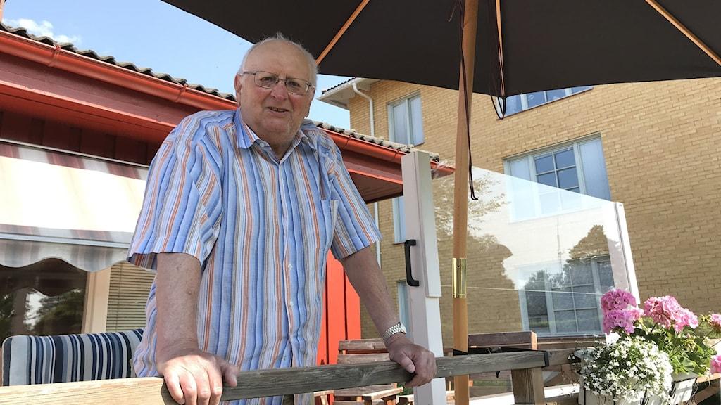 En äldre man står på en veranda med ett parasoll och plexiglas bredvid