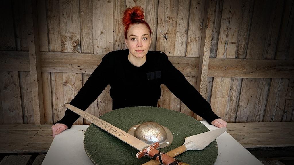 Kvinna med uppsatt rött hör framför vikingasköld och svärd.