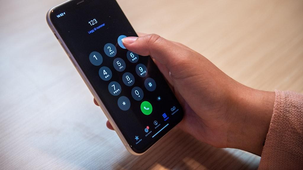 En person håller i en mobil.