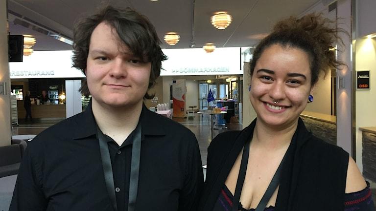 Två unga personer står i lobby.