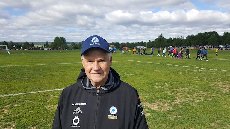 En man står på en fotbollsplan