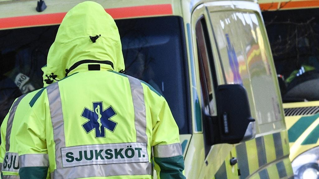 En ambulanssjuksköterska framför en ambulans