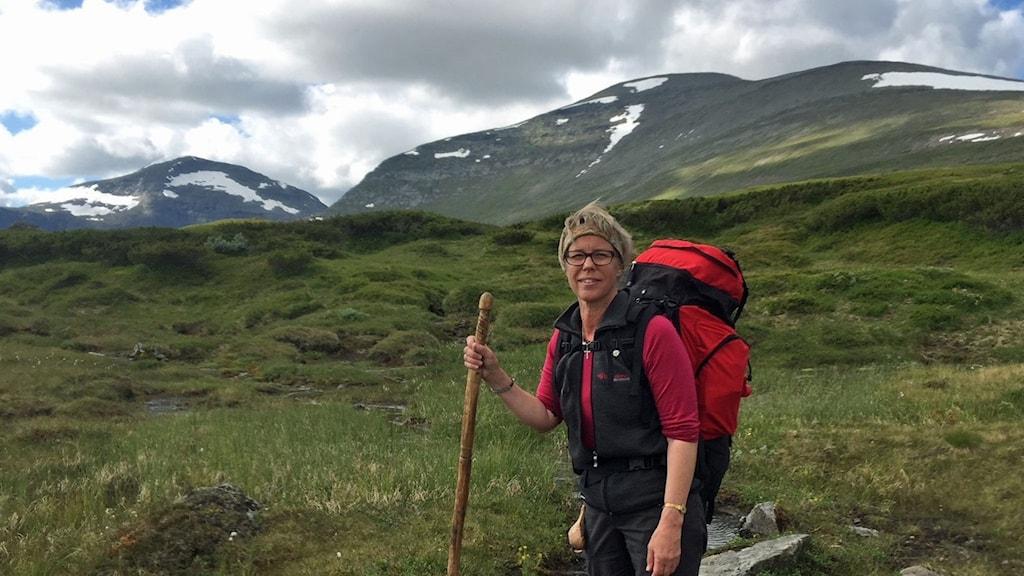 Dam med vandringsstav och fjälltopp i bakgrunden