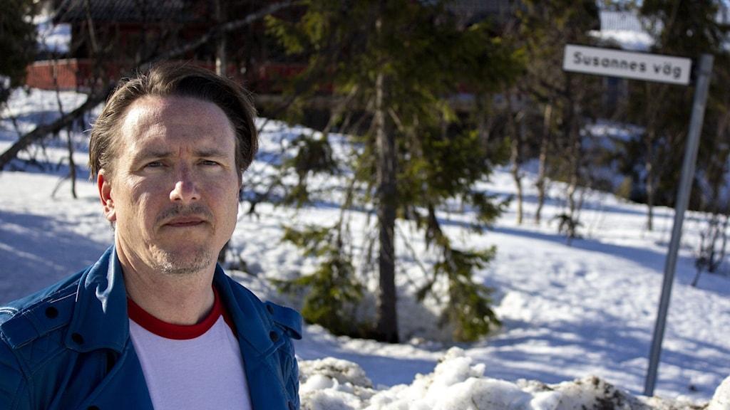 En man i vit t-shirt med röda detaljer med en blå jacka och vattenkammad frisyr