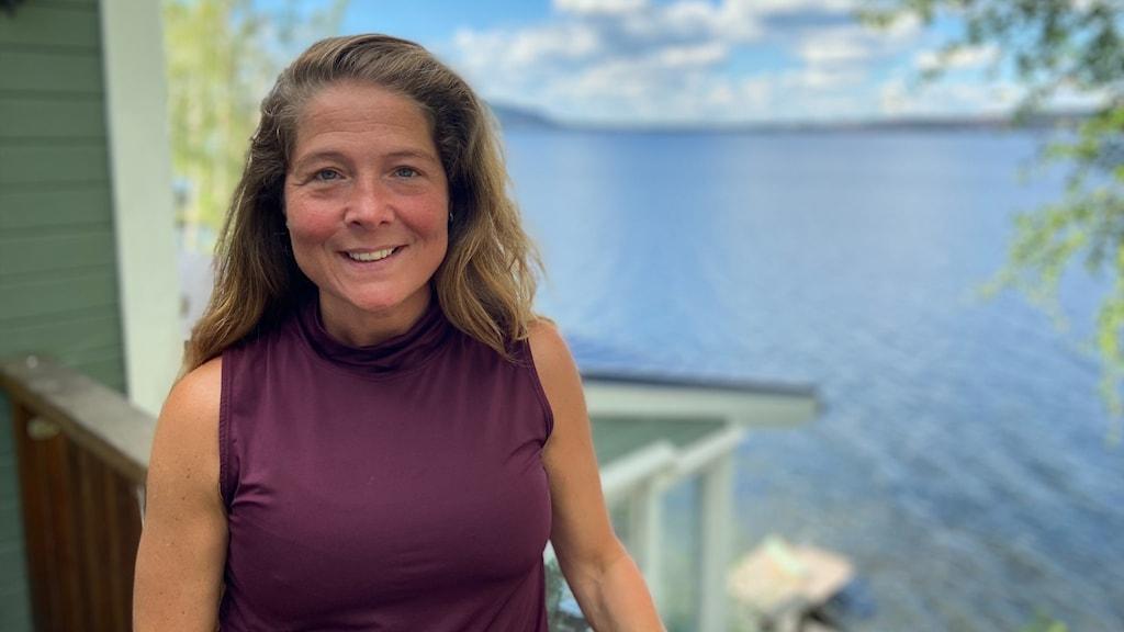 Kvinna står vid sjö och det är sommar