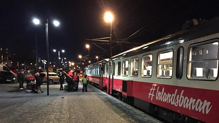 Ett tåg står vid en perrong och resenärer är på väg att gå ombord